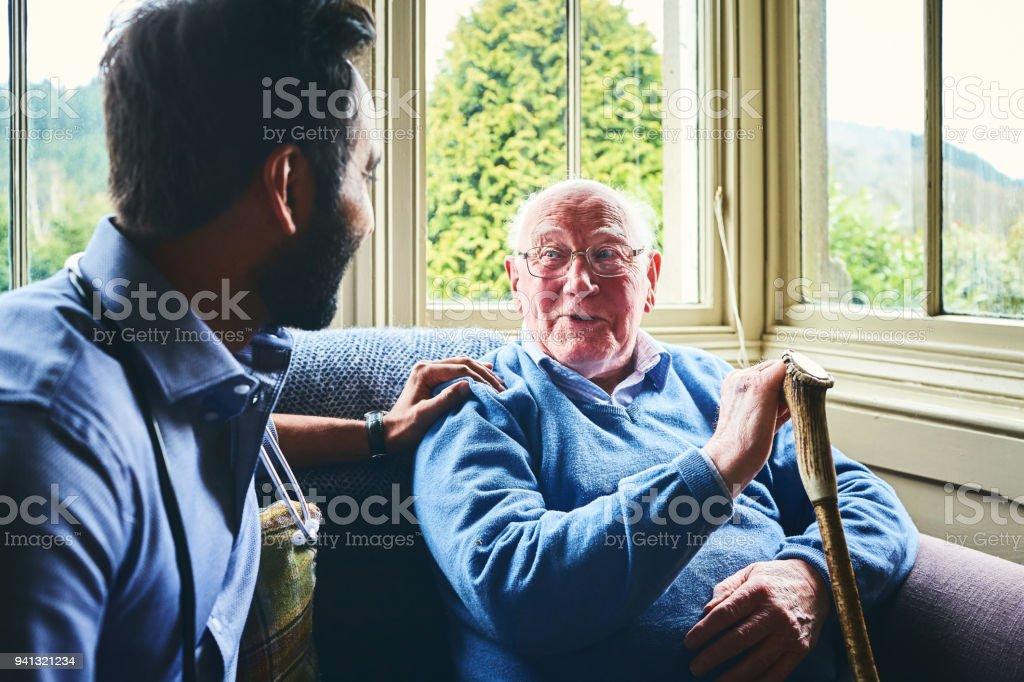 Arzt im Gespräch mit älteren Mann im Hausbesuch – Foto