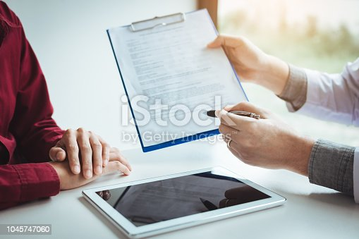 873418972istockphoto Doctor talking woth patient. 1045747060