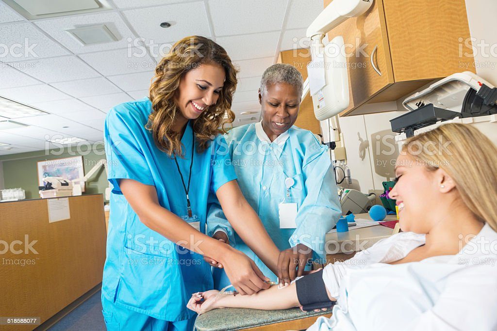 Doctor teaching nursing student to insert blood donation line stock photo
