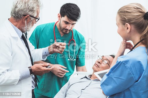 840514774istockphoto Doctor team taking care of senior adult man patient lying on bed in hospital ward. Medical healthcare staff service treatment concept. 1134710536
