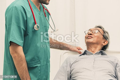 840514774istockphoto Doctor team taking care of senior adult man patient lying on bed in hospital ward. Medical healthcare staff service treatment concept. 1134710618