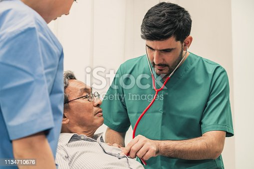 840514774istockphoto Doctor team taking care of senior adult man patient lying on bed in hospital ward. Medical healthcare staff service treatment concept. 1134710676