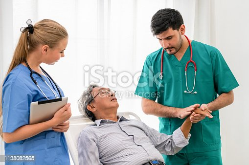 840514774istockphoto Doctor team taking care of senior adult man patient lying on bed in hospital ward. Medical healthcare staff service treatment concept. 1138082565