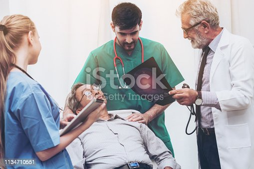 840514774istockphoto Doctor team work with x ray film image of the senior adult patient lying on the bed in the hospital ward room. Medical group teamwork and healthcare person staff service. 1134710551