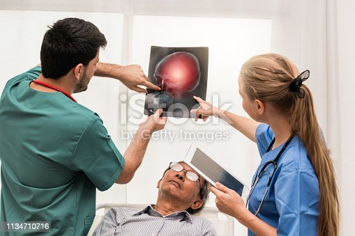 840514774istockphoto Doctor team work with x ray film image of the senior adult patient lying on the bed in the hospital ward room. Medical group teamwork and healthcare person staff service. 1134710716