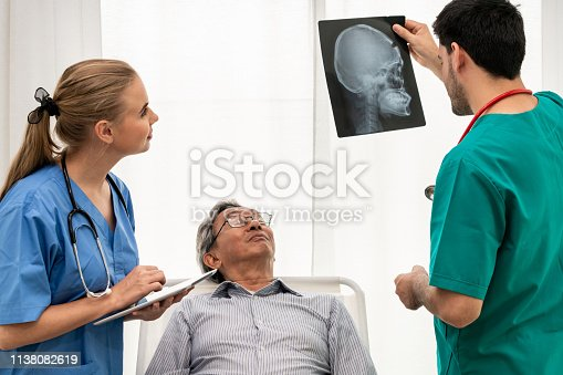 840514774istockphoto Doctor team work with x ray film image of the senior adult patient lying on the bed in the hospital ward room. Medical group teamwork and healthcare person staff service. 1138082619