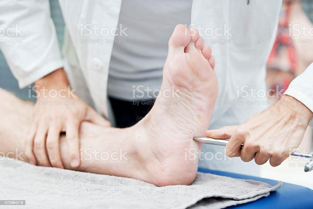 Doctor testing Babinski reflex stock photo