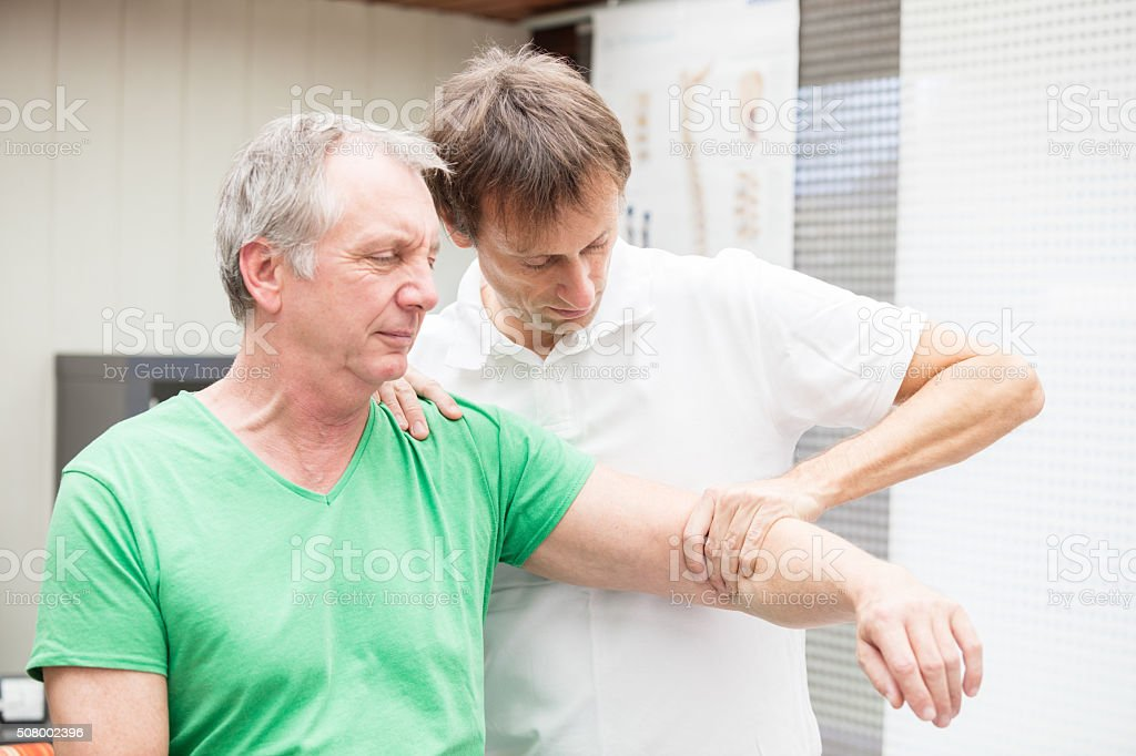 Doctor testing mobility of a patient`s shoulder stock photo