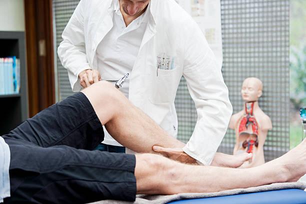Doctor testing patellatendon`s reflex stock photo