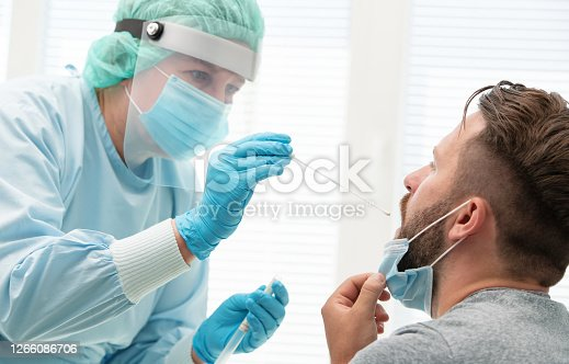 Doctor in a protective suit taking a throat and nasal swab from a patient to test for possible coronavirus infection