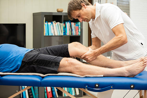 Doctor testing the knee with the Lachman Test stock photo