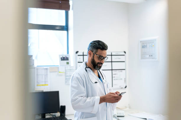 Doctor text messaging using phone in hospital stock photo