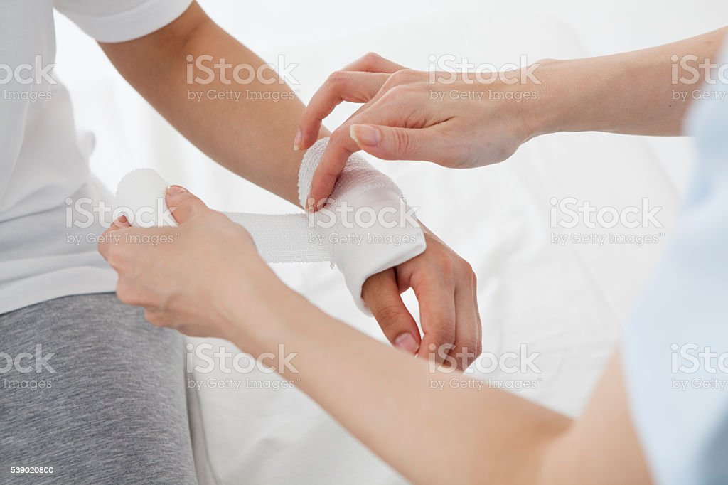 Doctor that benefits the hand of a patient with bandage stock photo