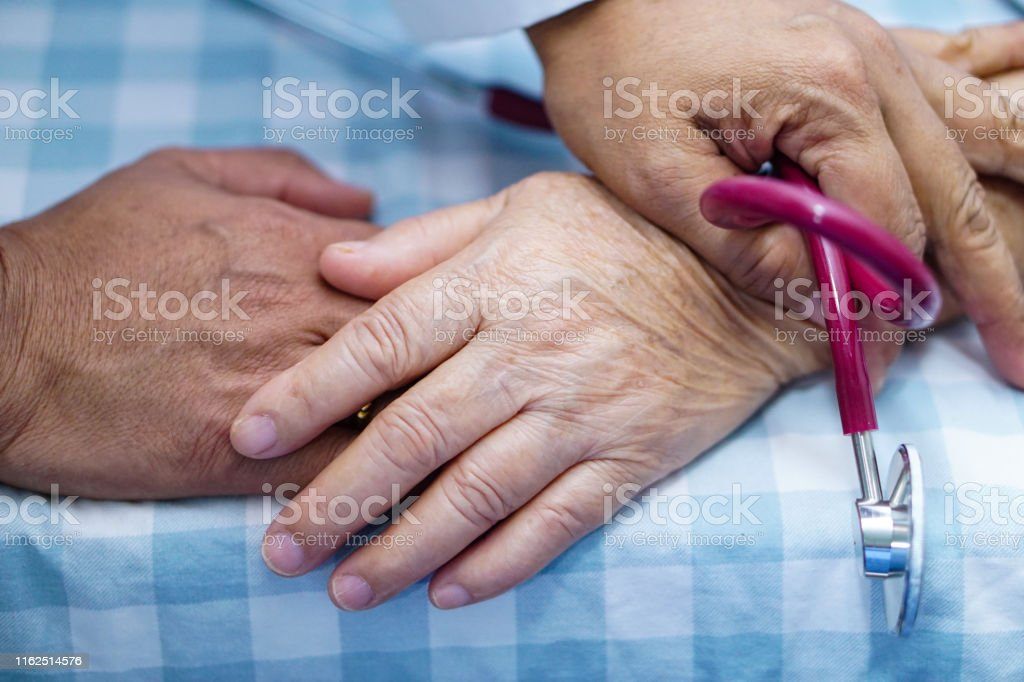 Doctor touching hands Asian senior or elderly old lady woman patient...