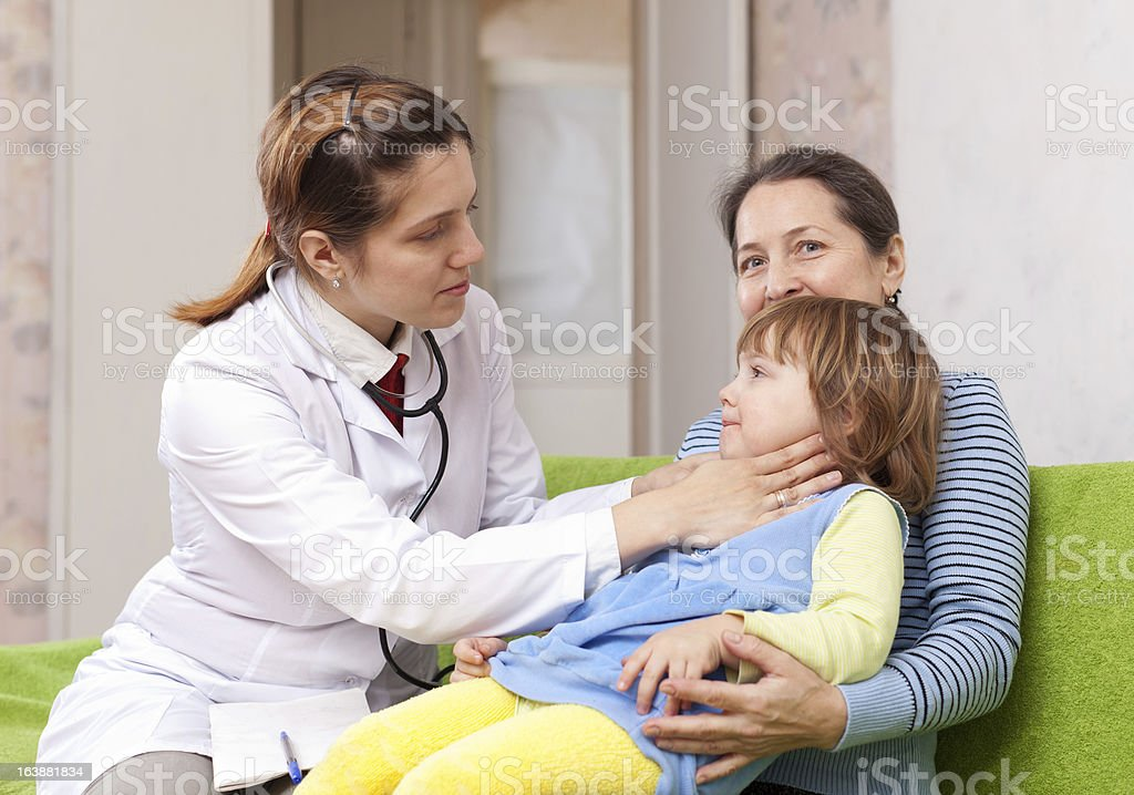 Doctor touching  neck of baby stock photo