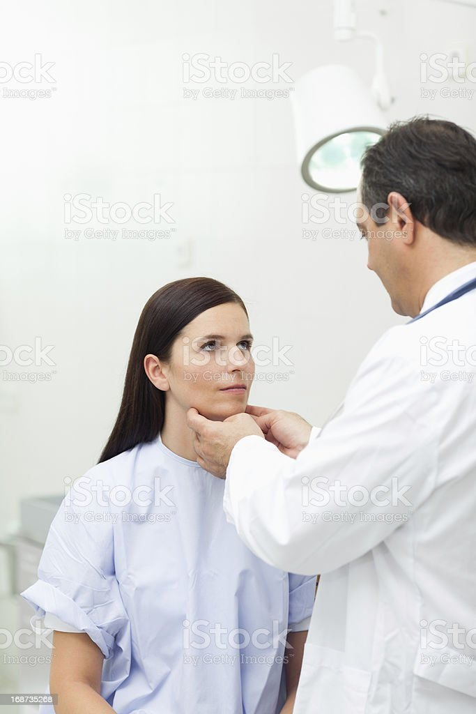 Doctor touching the neck of a patient stock photo