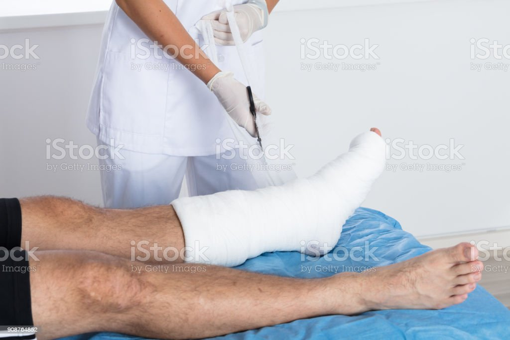 Close-up Of A Doctor\'s Hand Tying Bandage On Person\'s Foot In Clinic