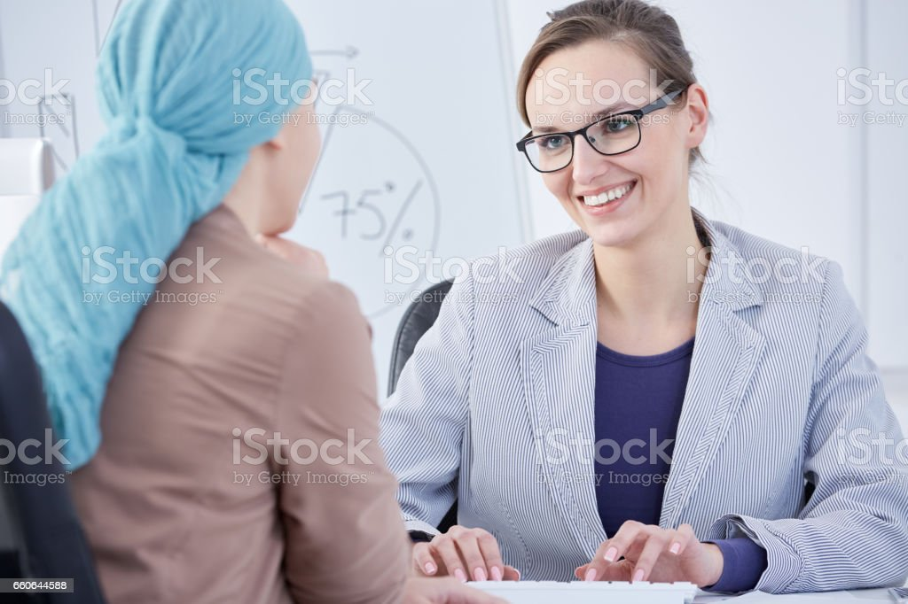 Doctor typing and talking to a patient stock photo