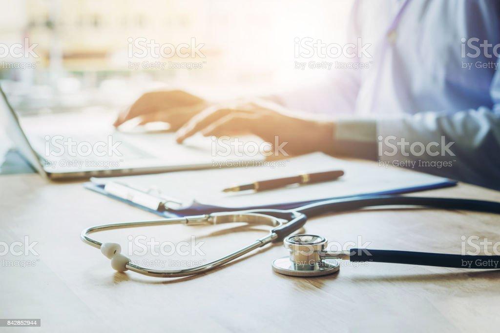 医者が聴診器を病院事務所中心にノート パソコンに情報を入力します。 - オフィスのロイヤリティフリーストックフォト