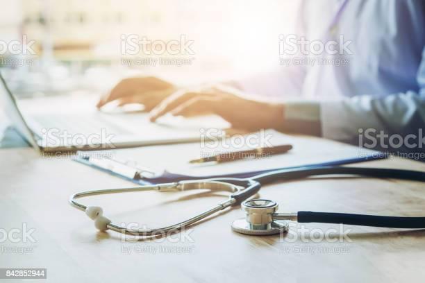 医者が聴診器を病院事務所中心にノート パソコンに情報を入力します - オフィスのストックフォトや画像を多数ご用意