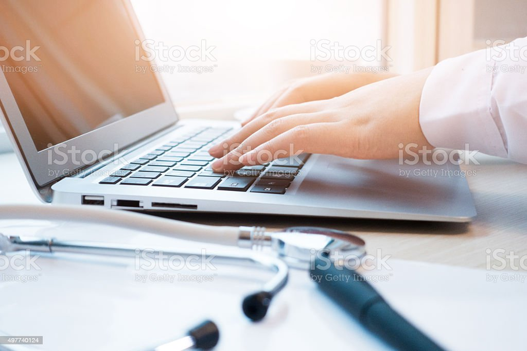 Doctor typing information on the computer in office stock photo