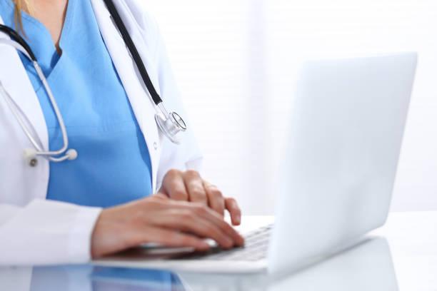 Arzt beim Sitzen auf dem Glasschreibtisch im Krankenhaus Büro auf Laptop-Computer eingeben. Arzt bei der Arbeit. Medizin und Pflege-Konzept – Foto