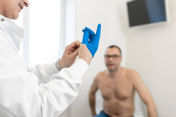 doctor urologist puts a medical glove on the arm to examine the patient's prostate, prostate massage, lymphatic drainage - prostate exam stock pictures, royalty-free photos & images