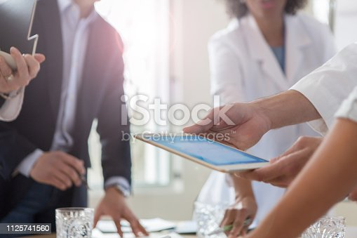 istock Doctor uses tablet during meeting 1125741560