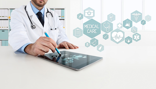 Doctor Uses The Tablet With Icons In Office Desk - Fotografie stock e altre immagini di Accudire