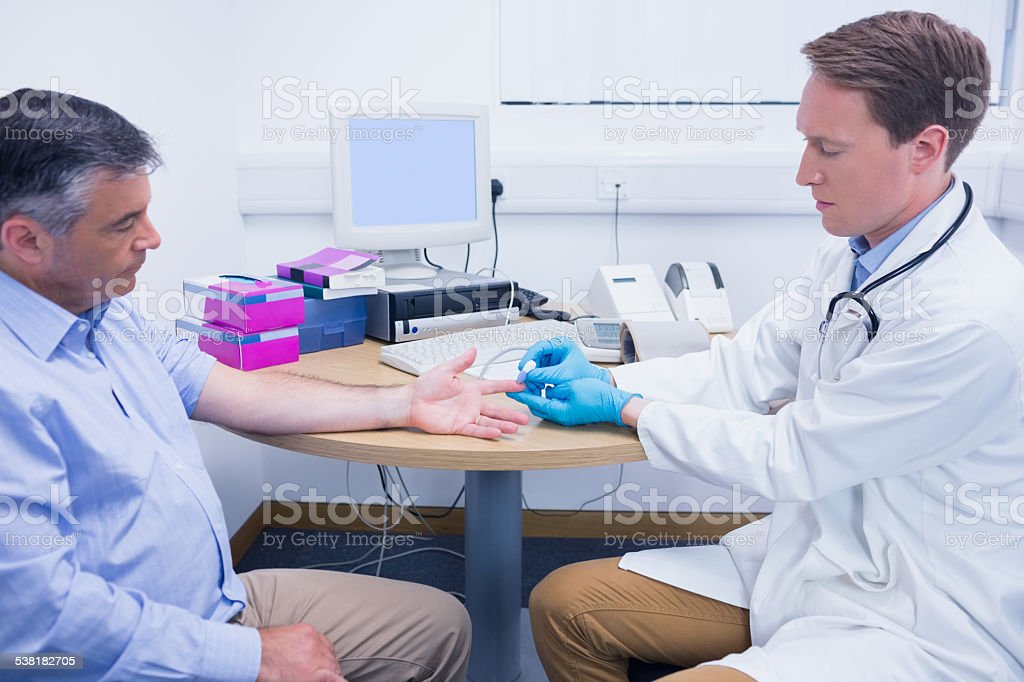 Doctor using a blood glucose meter stock photo