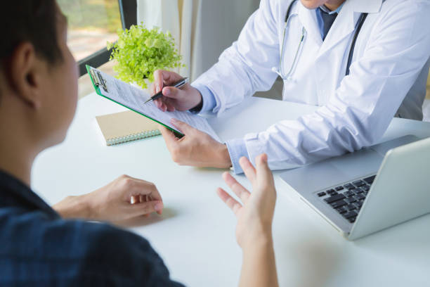Doctor using a clipboard to fill out a medical history of a young man's medication.doctor and patient discussing the results of a physical examination in a clinic