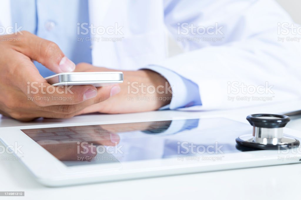 Doctor using a smartphone and a tablet stock photo