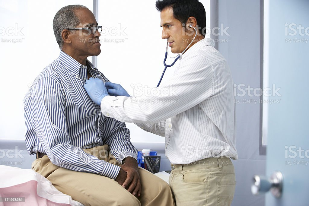 Doctor using a stethoscope on a patient listening to heart stock photo