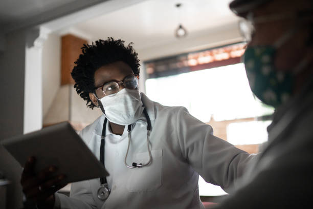 doctor using digital tablet and talking to patient at home - afro latino mask imagens e fotografias de stock
