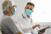 istock Doctor using digital tablet and talking to patient at home 1270643056