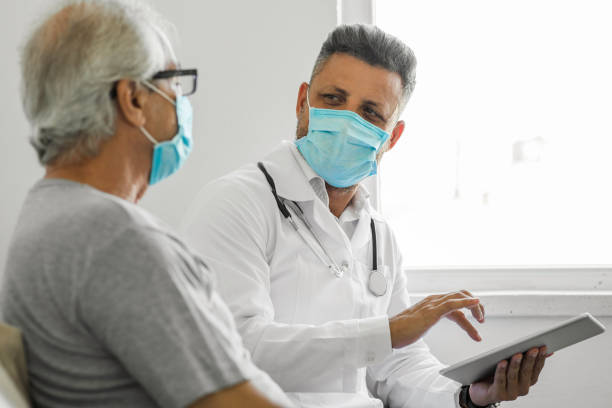Doctor using digital tablet and talking to patient at home stock photo