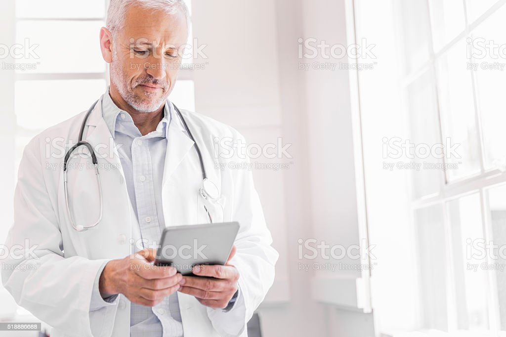 Doctor using digital tablet in brightly lit clinic stock photo