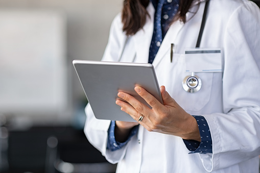 Close up of woman doctor hands using digital tablet at clinic. Closeup of female doctor in labcoat and stethoscope holding digital tablet, reading patient report. Hands holding medical report, copy space.