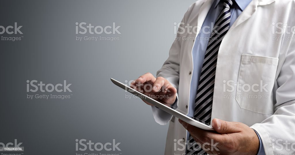 Doctor using digital tablet Doctor using digital tablet on gray background A Helping Hand Stock Photo
