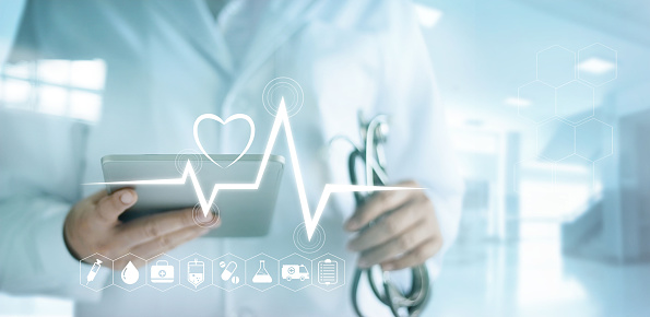 istock Doctor using digital tablet with medical icon and heartbeat rate in the hospital background 695337958