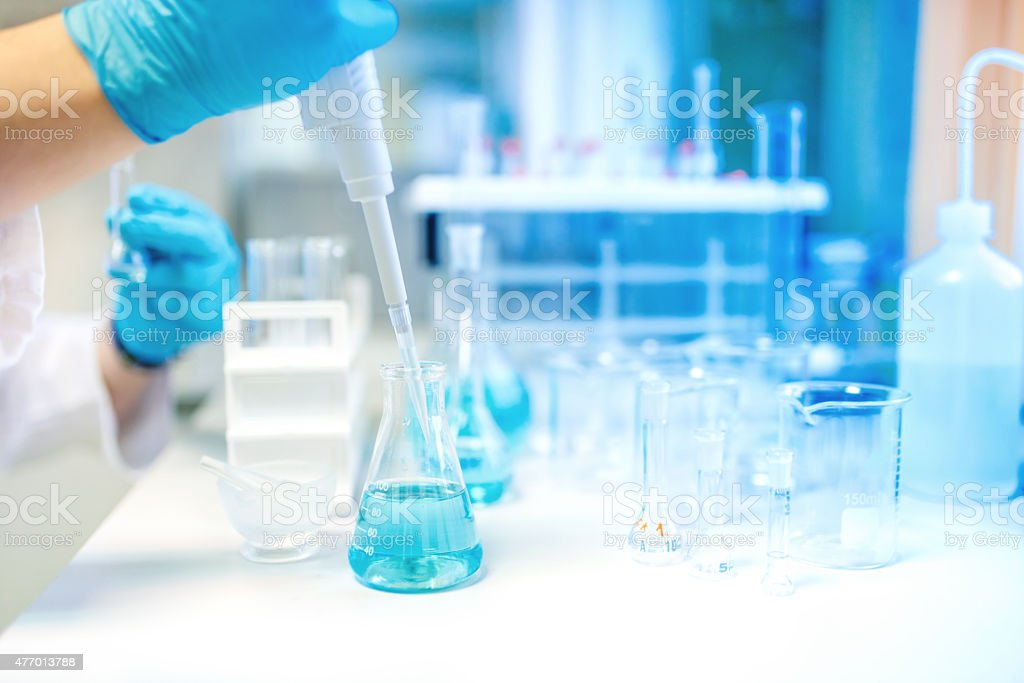 Doctor using electronic pipette for taking samples from test tube stock photo