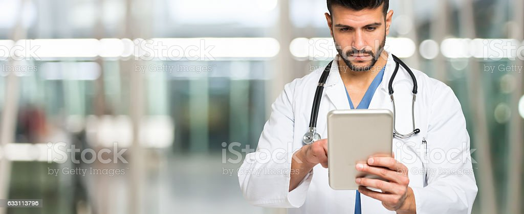 Doctor using his tablet. Large copy-space stock photo