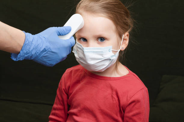 Doctor using infrared thermometer checking body temperature of little girl wearing surgical mask stock photo