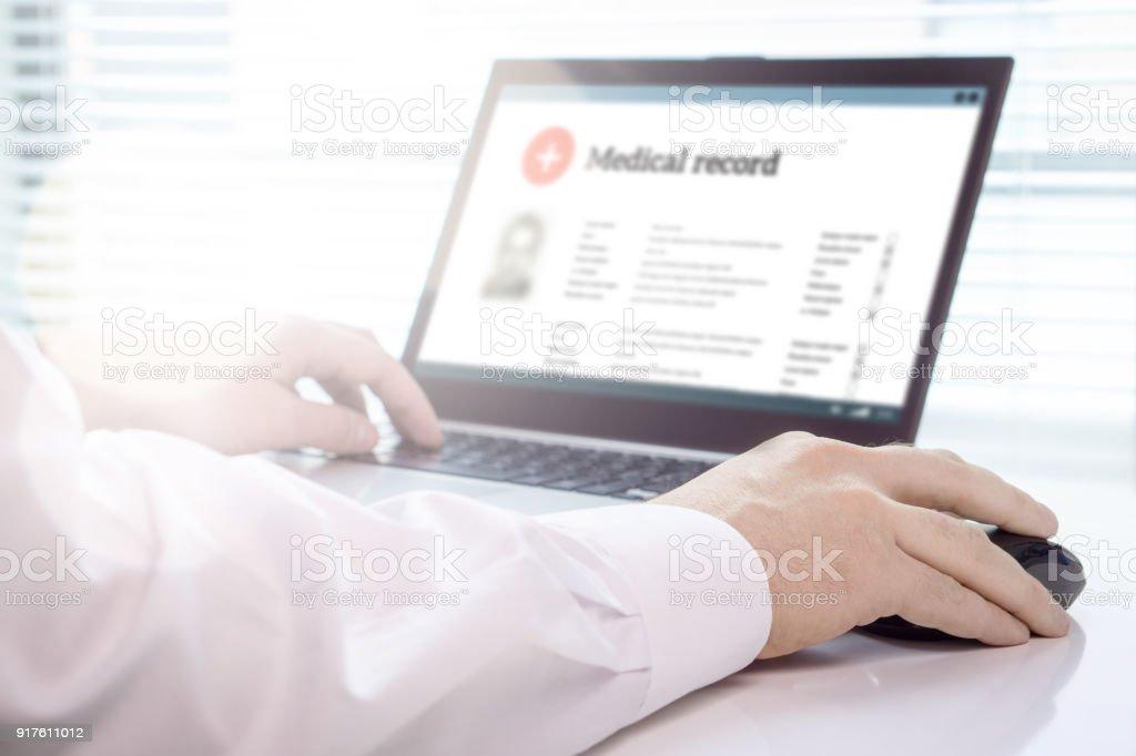 Médico con portátil y sistema de registro médico electrónico (EMR). Base de datos digital de salud del paciente y la información personal en pantalla de ordenador. - foto de stock