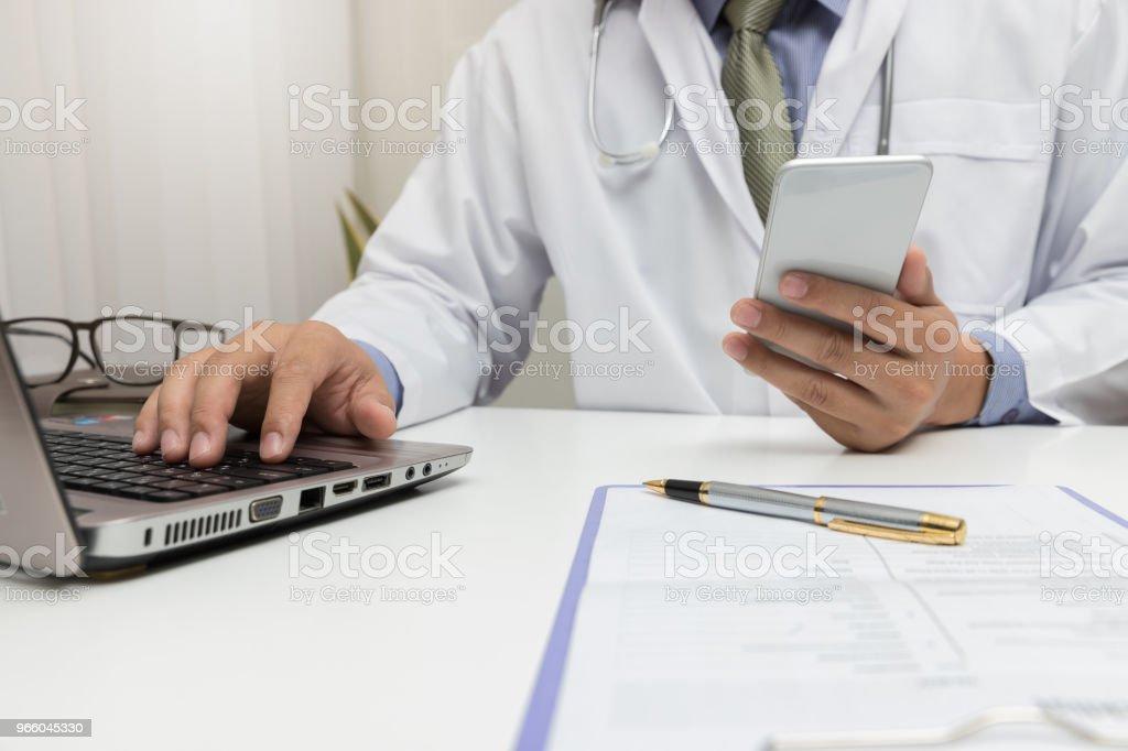 Arzt mit Laptop und Smartphone im Büro. - Lizenzfrei Analysieren Stock-Foto