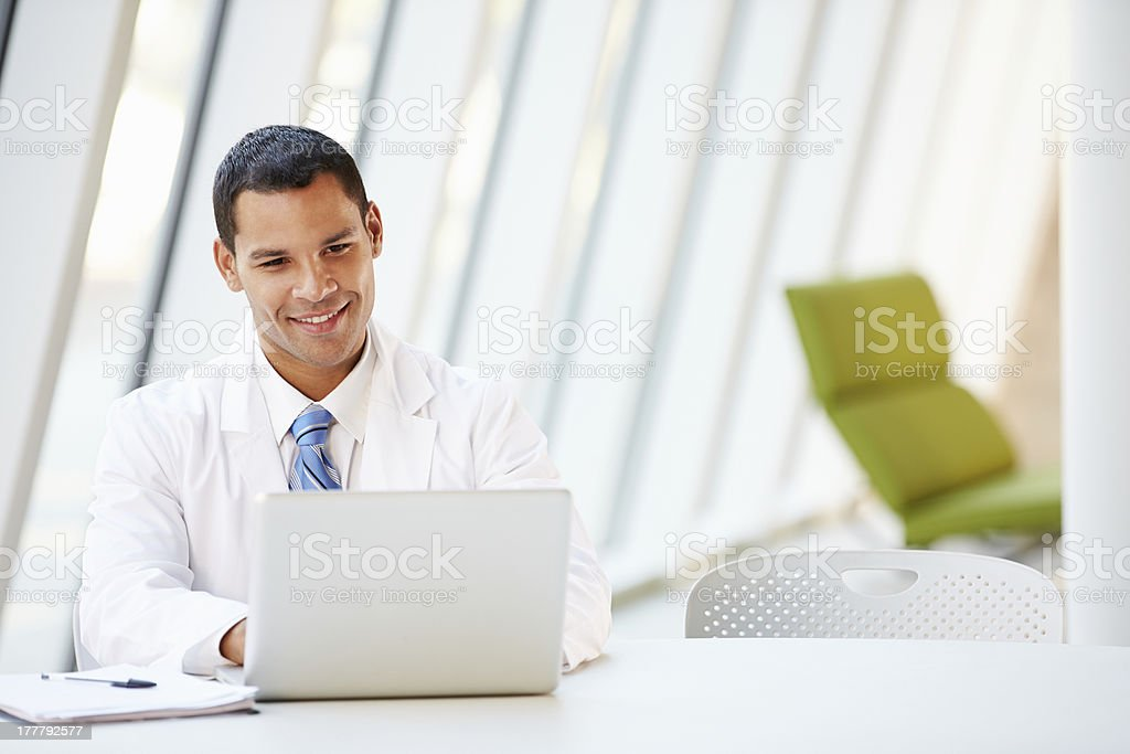 Arzt mit Laptop sitzt am Tisch In modernen Krankenhaus – Foto