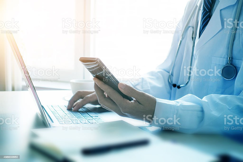 Doctor using smartphone in office stock photo