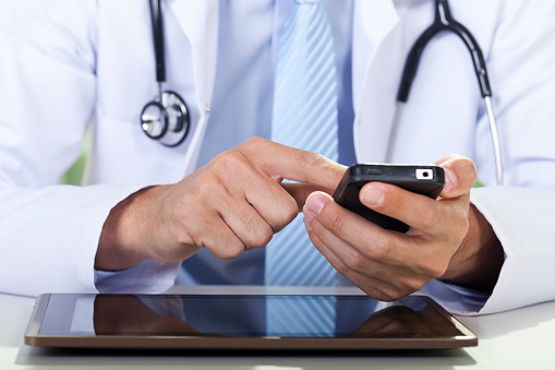Doctor Using Smartphone Stock Photo - Download Image Now