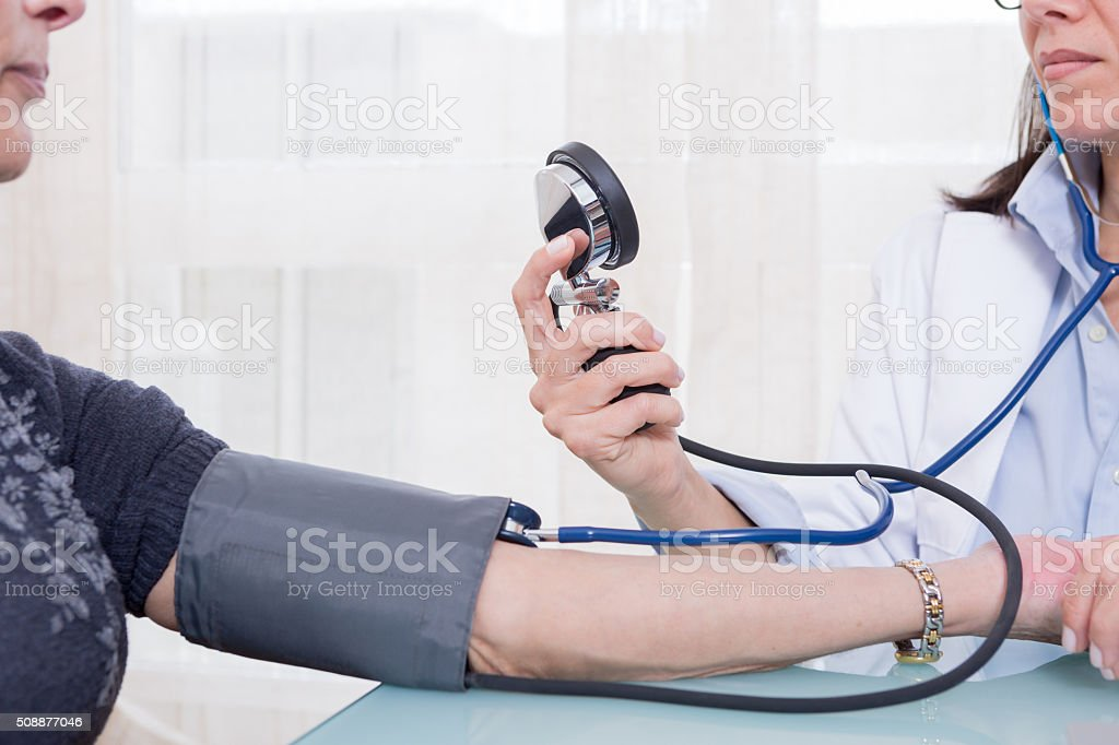 Doctor using sphygmomanometer and stethoscope stock photo
