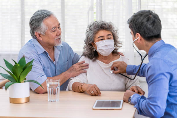Doctor using stethoscope for auscultate Asian grandparent patient in house